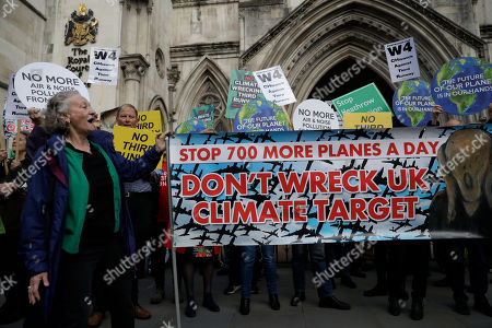 Politician Jenny Jones, Britain's Green Party representative in the House of Lords, looks at a banner as she joins campaigners protesting against British government plans to expand Heathrow Airport through the construction of a third runway, outside the Royal Courts of Justice on the first day of their legal appeal hearing in London, . A coalition of local councils, environmentalists and London residents claim the government has failed to properly address the impact on air quality, climate change, noise and congestion that expansion would bring