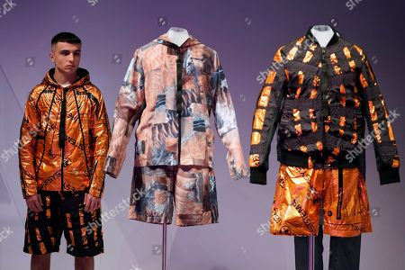 A model poses for photographs next to clothes designed by British designer Christopher Raeburn during the 'Moving to Mars' exhibition at the Design Museum in London, Britain, 17 October 2019. The exhibition examines the future of space exploration and living in Mars.