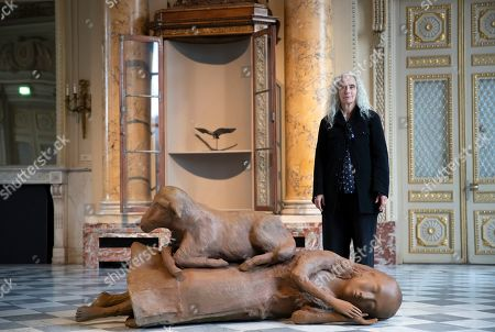 US artist Kiki Smith poses next to her artwork entitled 'Sleeping, Wandering, Slumber, Looking About, Rest Upon' during the press visit of her exhibition 'Kiki Smith' held at the Monnaie de Paris, in Paris, France, 17 October 2019. The exhibition runs from 18 October to 09 February 2020.