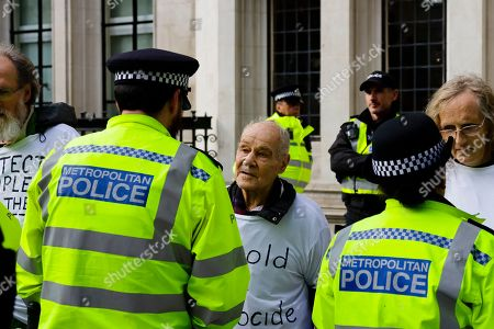 Stock Picture of British police address 91 year-old Eric Levy, an Extinction Rebellion protester glued to his fellow protesters outside the Supreme Court.