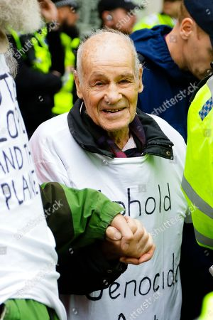 Extinction Rebellion protester Eric Levy smiles while police work to unglue his hand from that of a fellow protester outside the Supreme Court.