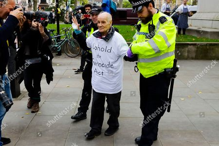 91 year-old Extinction Rebellion protester Eric Levy is photographed as he is arrested after glueing himself to his fellow protesters outside the Supreme Court.