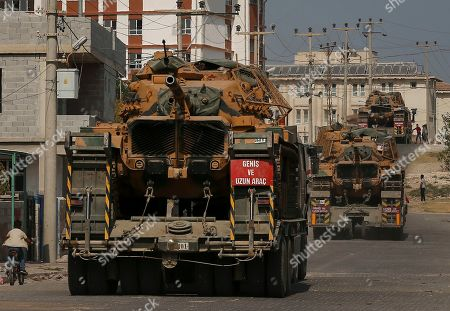 Turkish army tanks are transported on trucks in the outskirts of the town of Akcakale, in Sanliurfa province, southeastern Turkey, at he border of Syria, . U.S. Vice President Mike Pence, heading a delegation that includes Secretary of State Mike Pompeo and White House national security adviser Robert O'Brien, arrived in Turkey on Thursday, a day after Trump dismissed the very crisis he sent his aides on an emergency mission to douse
