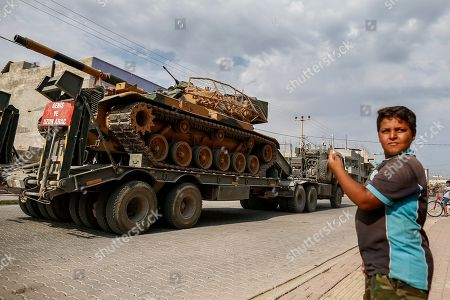 A child watches as army tanks are transported on trucks in the outskirts of the town of Akcakale, in Sanliurfa province, southeastern Turkey, at he border of Syria, . U.S. Vice President Mike Pence, heading a delegation that includes Secretary of State Mike Pompeo and White House national security adviser Robert O'Brien, arrived in Turkey on Thursday, a day after Trump dismissed the very crisis he sent his aides on an emergency mission to douse