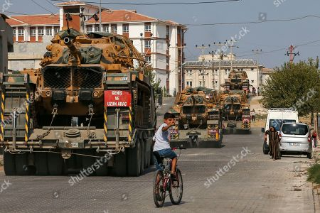 Children watch as army tanks are transported on trucks in the outskirts of the town of Akcakale, in Sanliurfa province, southeastern Turkey, at he border of Syria, . U.S. Vice President Mike Pence, heading a delegation that includes Secretary of State Mike Pompeo and White House national security adviser Robert O'Brien, arrived in Turkey on Thursday, a day after Trump dismissed the very crisis he sent his aides on an emergency mission to douse