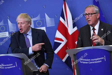 British Prime Minister Boris Johnson and European Commission President Jean-Claude Juncker make prepared statements during a press point at EU headquarters in Brussels, . Britain and the European Union reached a new tentative Brexit deal on Thursday, hoping to finally escape the acrimony, divisions and frustration of their three-year divorce battle