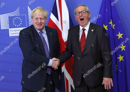 British Prime Minister Boris Johnson shakes hands with European Commission President Jean-Claude Juncker during a press point at EU headquarters in Brussels, . Britain and the European Union reached a new tentative Brexit deal on Thursday, hoping to finally escape the acrimony, divisions and frustration of their three-year divorce battle