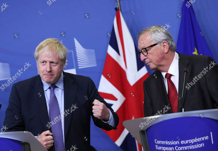 British Prime Minister Boris Johnson gestures as he stands alongside European Commission President Jean-Claude Juncker during a press point at EU headquarters in Brussels, . Britain and the European Union reached a new tentative Brexit deal on Thursday, hoping to finally escape the acrimony, divisions and frustration of their three-year divorce battle