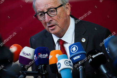 European Commission President Jean-Claude Juncker talks to journalists as he arrives for an EU summit at the Europa building in Brussels, . Britain and the European Union reached a new tentative Brexit deal on Thursday, hoping to finally escape the acrimony, divisions and frustration of their three-year divorce battle