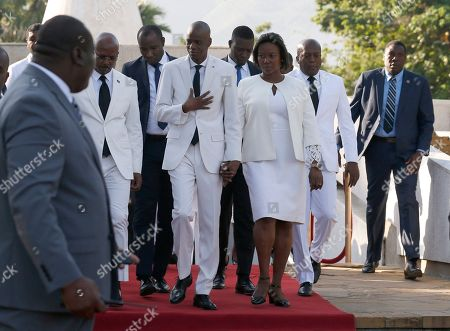 Stock Picture of Accompanied by First Lady Martine Moïse, center right, and and acting prime minister Jean Michel Lapin, center left, President Jovenel Moise, center, arrives to lay flowers to mark the anniversary of the death of Haitian revolution leader Jean Jacques Dessalines, in Champ de Mars, adjacent to the National Palace, in Port-au-Prince, Haiti, . President Moise has been facing ever more violent protests demanding his resignation fueled by anger over corruption, inflation and dwindling of basic supplies, including gasoline