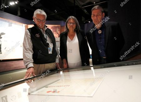 """Kevin Gover, Chief Beverly Kiohawiton Cook, Chief Eric Tehoroniathe Thompson. Kevin Gover, left, Director of the National Museum of the American Indian, and Chief Beverly Kiohawiton Cook, center, and Chief Eric Tehoroniathe Thompson, right, of the St. Regis Band of Mohawk Indians view the 1784 Treaty of Fort Stanwix at the Smithsonian's National Museum of the American Indian on in Washington. The treaty, on loan from the National Archives, was signed Oct. 22, 1784, at Fort Stanwix near present-day Rye, New York. It goes on view today in the exhibition """"Nation to Nation: Treaties Between the United States and American Indian Nations"""
