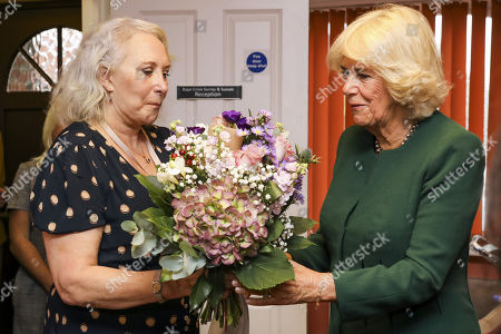Stock Image of Yvonne Traynor (L), CEO of Rape Crisis Centre for Surrey and Sussex (RCSAS) gives a bouquet of flowers to Camilla Duchess of Cornwall as she visits the centre on October 17, 2019 in Crawley, United Kingdom. The visit marks the 10th year anniversary since the Duchess first visited the Rape Crisis Centre in South London based in Croydon in November 2009.