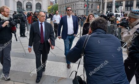Andrey Kukushkin, center, leaves federal court, in New York. Kukushkin and David Correia pleaded not guilty Thursday to conspiring with associates of Rudy Giuliani to make illegal campaign contributions. They are among four men charged with using straw donors to make illegal contributions to politicians they thought could help their political and business interests
