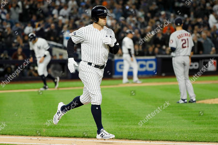 Houston Astros starting pitcher Zack Greinke, right, walks New York Yankees center fielder Brett Gardner scoring Aaron Judge, left, during the first inning in Game 4 of baseball's American League Championship Series, in New York