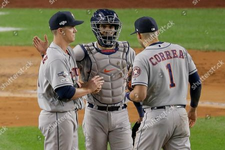 Houston Astros starting pitcher Zack Greinke, left, stands on the mound with catcher Robinson Chirinos, center, and shortstop Carlos Correa (1) after walking New York Yankees' Brett Gardner with the bases loaded during the first inning of Game 4 of baseball's American League Championship Series, in New York