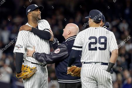 New York Yankees trainer Steve Donohue, center, checks on pitcher CC Sabathia during the eighth inning of Game 4 of baseball's American League Championship Series against the Houston Astros, in New York
