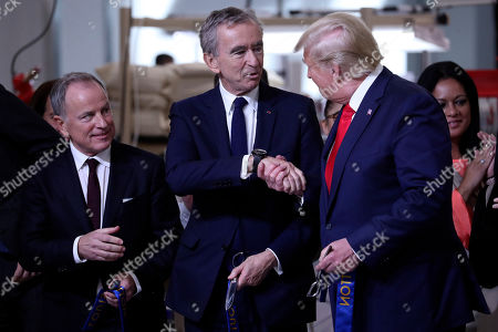 Stock Photo of President Donald Trump shakes hands with Bernard Arnault, chief executive of LVMH, during a ribbon cutting ceremony at the Louis Vuitton Workshop Rochambeau in Alvarado, Texas,. At left is Michael Burke, chairman and chief executive officer of of Louis Vuitton - LVMH