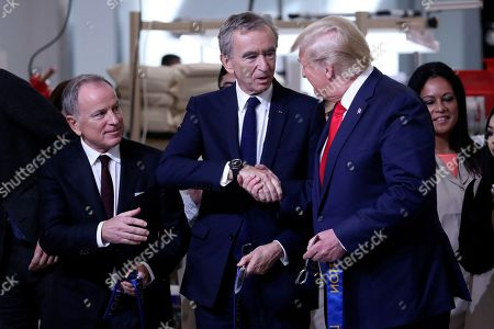 President Donald Trump shakes hands with Bernard Arnault, chief executive of LVMH, during a ribbon cutting ceremony at the Louis Vuitton Workshop Rochambeau in Alvarado, Texas,. At left is Michael Burke, chairman and chief executive officer of of Louis Vuitton - LVMH