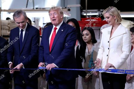 President Donald Trump cuts a ribbon with Bernard Arnault, chief executive of LVMH, at the Louis Vuitton Workshop Rochambeau in Alvarado, Texas,. At right is Ivanka Trump