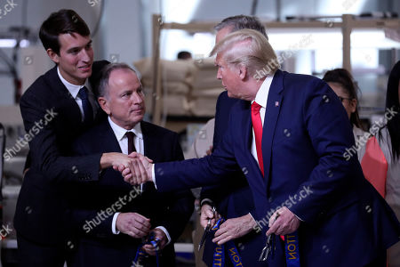 President Donald Trump shakes hands with Alexandre Arnault during a ribbon cutting ceremony at the Louis Vuitton Workshop Rochambeau in Alvarado, Texas,. At center is Michael Burke, chairman and chief executive officer of of Louis Vuitton - LVMH