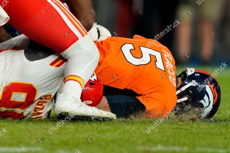 Denver Broncos quarterback Joe Flacco (5) is sacked by Kansas City Chiefs defensive end Emmanuel Ogbah during the second half of an NFL football game, in Denver