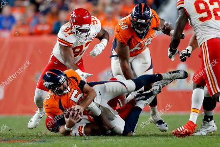 Denver Broncos quarterback Joe Flacco (5) is sacked by Kansas City Chiefs defensive end Emmanuel Ogbah (90) during the second half of an NFL football game, in Denver