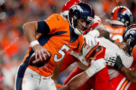 Denver Broncos quarterback Joe Flacco (5) scrambles against the Kansas City Chiefs during the first half of an NFL football game, in Denver