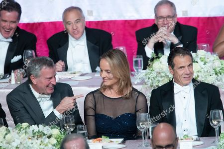 Stock Picture of Bill de Blasio, Maureen Sherry Klinsky, Andrew Cuomo. New York City Mayor Bill de Blasio, left, Maureen Sherry Klinsky, center, and New York Gov. Andrew Cuomo react to opening remarks during the 74th Annual Alfred E. Smith Memorial Foundation Dinner, in New York
