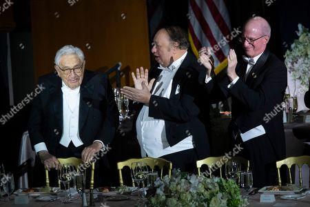 Stock Photo of Henry Kissinger, John Catsimatidis, James S. Tisch. John Catsimatidis, center, and James S. Tisch, right, applaud as former U.S. Secretary of State Henry Kissinger arrives for the 74th Annual Alfred E. Smith Memorial Foundation Dinner, in New York