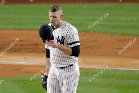 New York Yankees starting pitcher James Paxton adjusts his cap betweeing pitches against the Houston Astros during the first inning of Game 5 of baseball's American League Championship Series, in New York