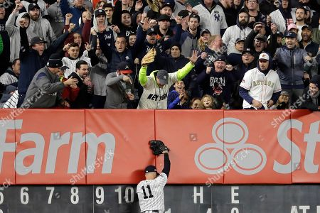 New York Yankees fans react after New York Yankees center fielder Brett Gardner (11) caught a deep fly ball by Houston Astros Robinson Chirinos at the wall to end the top of the sixth inning of Game 5 of baseball's American League Championship Series, in New York