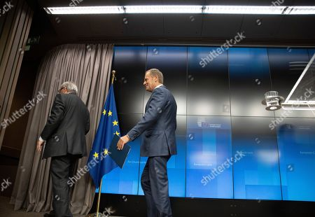 European Commission President Jean-Claude Juncker, left, and European Council President Donald Tusk leave the podium at the end of a media conference at an EU summit in Brussels, . After agreeing on terms for a new Brexit deal, European Union leaders are meeting again to discuss other thorny issues including the bloc's budget and climate change