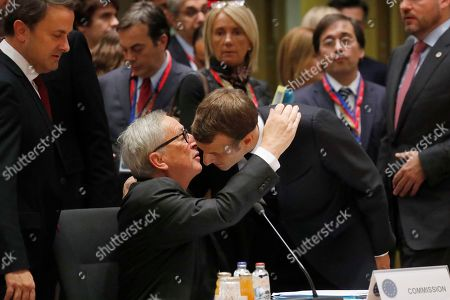 European Commission President Jean-Claude Juncker, center left, greets French President Emmanuel Macron, center right, during a round table meeting at EU summit in Brussels, . After agreeing on terms for a new Brexit deal, European Union leaders are meeting again to discuss other thorny issues including the bloc's budget and climate change