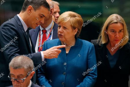 German Chancellor Angela Merkel, center, speaks with Spanish Prime Minister Pedro Sanchez, left, during a round table meeting at EU summit in Brussels, . After agreeing on terms for a new Brexit deal, European Union leaders are meeting again to discuss other thorny issues including the bloc's budget and climate change