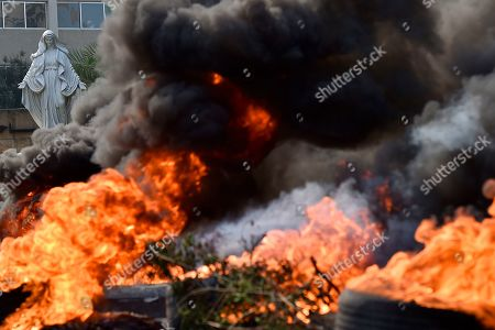 Stock Picture of A statue of the Virgin Mary is seen in the background as the black smoke rises from burning tires set by protesters to block a Dora highway during a protest in north of Beirut, Lebanon, 18 October 2019. Protesters, mainly civil activists, started to demonstrate in downtown Beirut on 17 October, condemning the proposed taxes that would go along with the 2020 budget, especially an unexpected government plan to impose a fee of 0.20 cents a day for using WhatsApp calls. This charge will not make it through the government palace according to the Telecommunications Minister Mohamed Choucair after witnessing the impact this made on the streets.