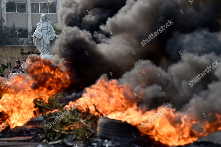 A protester stands near the statue of the Virgin Mary as the black smoke rises from burning tires set by protesters to block a Dora highway during a protest in north of Beirut, Lebanon, 18 October 2019. Protesters, mainly civil activists, started to demonstrate in downtown Beirut on 17 October, condemning the proposed taxes that would go along with the 2020 budget, especially an unexpected government plan to impose a fee of 0.20 cents a day for using WhatsApp calls. This charge will not make it through the government palace according to the Telecommunications Minister Mohamed Choucair after witnessing the impact this made on the streets.