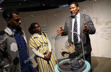 The grandson of Nelson Mandela, Nkosi Zwelivelile Mandela ('Chief Mandela') shows a ceremonial leopard-skin headdress awarded to his grandfather to German presenter Patrice Bouedibela (L) and German singer Ivy Quainoo, as part of the exhibition MANDELA: THE OFFICIAL EXHIBITION in Berlin, Germany, 18 October 2019. The exposition is a new global touring exhibition that shows Mandela's life from his struggles as a freedom fighter to that of a political leader.