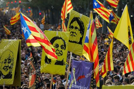Protestors hold pictures of Catalan high-profile separatist politicians, Clara Ponsati, Anna Gabriel and Carles Puidgemont, from left to right, who are fugitives from Spanish law after fleeing the country, during a demonstration in Barcelona, Spain, .The Catalan regional capital is bracing for a fifth day of protests over the conviction of a dozen Catalan independence leaders. Five marches of tens of thousands from inland towns are converging in Barcelona's center for a mass protest