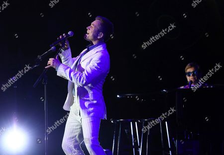 Taron Egerton, Elton John. Taron Egerton, left, and Sir Elton John perform at Paramount Pictures' Rocketman: Live in Concert presented by Black Ink at the Greek Theater on in Los Angeles
