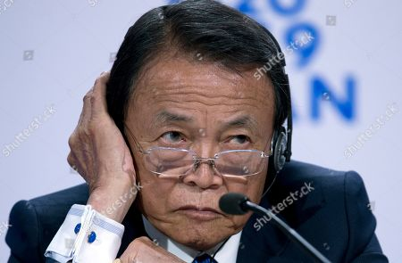 Japan's Finance Minister Taro Aso listens during a news conference in the sidelines of the World Bank/IMF Annual Meetings in Washington