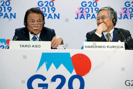 Japan's Finance Minister Taro Aso, left, accompanied by Bank of Japan Governor Haruhiko Kuroda, speak during a news conference in the sidelines of the World Bank/IMF Annual Meetings in Washington