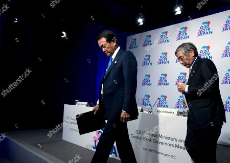 Japan's Finance Minister Taro Aso, left, accompanied by Bank of Japan Governor Haruhiko Kuroda, leave after speaking in a news conference on the sidelines of the World Bank/IMF Annual Meetings in Washington