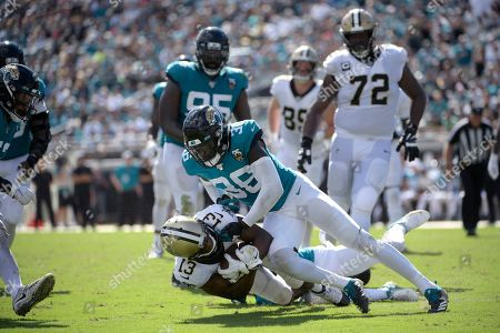 New Orleans Saints wide receiver Michael Thomas (13) is tackled by Jacksonville Jaguars cornerback A.J. Bouye (21) and defensive back Ronnie Harrison (36) after catching a pass during the second half of an NFL football game, in Jacksonville, Fla