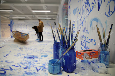 People view the interactive installation 'Add Color (Refugee Boat)' by Japanese-US artist Yoko Ono, made up of an empty room with a boat where visitors can paint messages and images on the walls, in Dortmund, Germany, 18 October 2019. Performance artist Yoko Ono presented her work at a conference of the Erich Brost Institute for International Journalism at the TU Dortmund where some 90 journalism trainers from 30 European and African countries will discuss reporting on migration and flight.