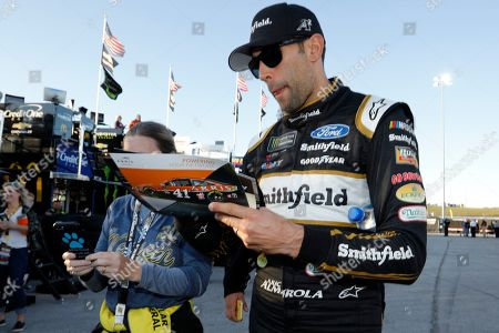 Aric Almirola signs autographs before practice for the NASCAR Cup Series auto race at Kansas Speedway in Kansas City, Kan