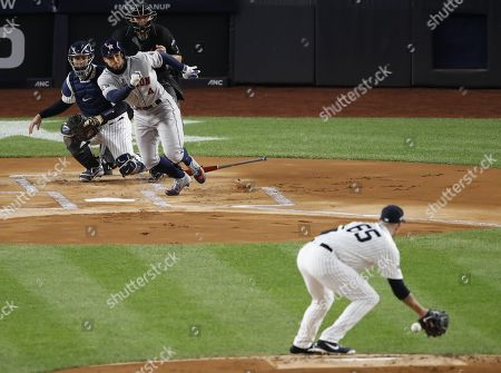 Houston Astros George Springer (C) hits a single past New York Yankees starting pitcher James Paxton (R) during the top of the first inning of a Major League Baseball American League Championship Series playoff baseball game five at Yankees Stadium in New York, 18 October 2019.