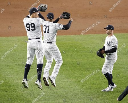 Stock Picture of New York Yankees center fielder Aaron Hicks (C) and New York Yankees right fielder Aaron Judge (L) celebrate as New York Yankees center fielder Brett Gardner (R) looks on after defeating the Houston Astros during the Major League Baseball American League Championship Series playoff baseball game five at Yankees Stadium in New York, New York, 18 October 2019.