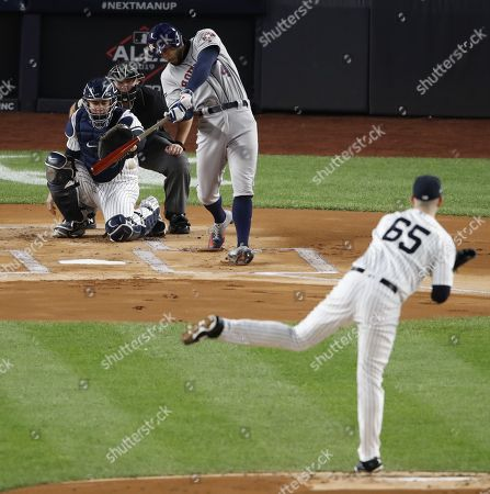 Stock Photo of Houston Astros George Springer (C) hits a single off New York Yankees starting pitcher James Paxton (R) during the top of the first inning of a Major League Baseball American League Championship Series playoff baseball game five at Yankees Stadium in New York, 18 October 2019.