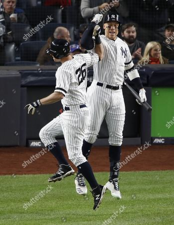 New York Yankees DJ LeMahieu (L) is greeted by New York Yankees Aaron Judge (R) after hitting a solo home run off Houston Astros starting pitcher Justin Verlander during the the first inning of the Major League Baseball American League Championship Series playoff baseball game five at Yankees Stadium in New York, New York, 18 October 2019.