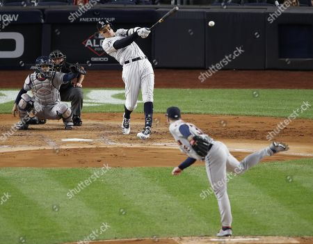 New York Yankees Aaron Judge (C) follows through with a single off Houston Astros starting pitcher Justin Verlander (R) during the the first inning of the Major League Baseball American League Championship Series playoff baseball game five at Yankees Stadium in New York, New York, 18 October 2019.